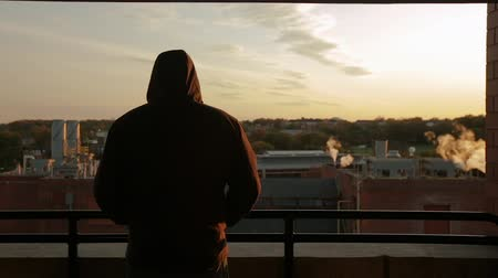 durulması : Man in a hooded jacket looking over an industrial city or town as the sun is setting. Silhouette