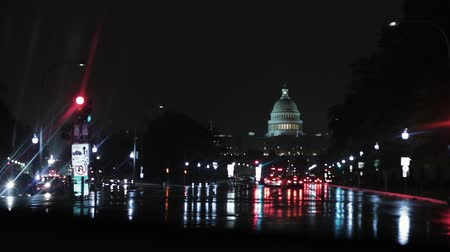 Rainy night driving in Washington D.C. Capital city. Stopped at stoplight, Capitol Building in the background.