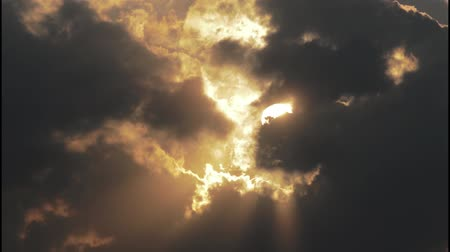 equinox : Evening sun casting rays trough dark and slowly moving clouds Stock Footage