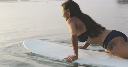 getting ready : sexy fit sporty brunette girl or tanned woman or female surfer lying on surfboard, getting ready to surf. summertime travel, vacation. ocean or sea around