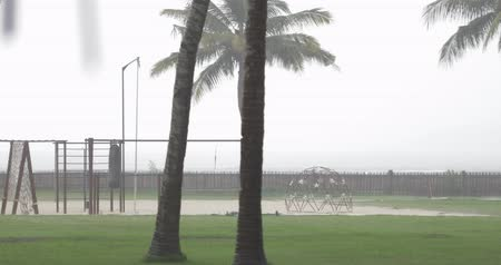 západ : nice playground (sport area) on the coast, rainy cloudy weather in south country, sea or ocean waves on background
