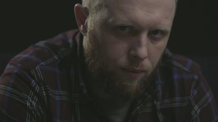 deep eyes : close-up portrait of a strong brutal man with a beard. piercing glance at the camera. looking away and looking at the camera after Stock Footage