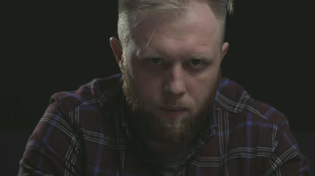 deep eyes : closeup bearded ginger nice man (guy) sitting, wearing plaid shirt, killing with his eyes. black background