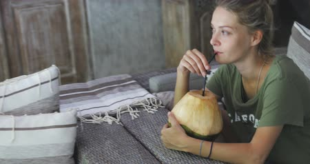 plavé vlasy : young happy funny good looking girl or woman with fair hair sitting on and drinking coconut water on couch, enjoying her time Dostupné videozáznamy