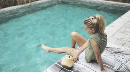 plavé vlasy : slim healthy pretty girl or woman sitting on the edge of swimming pool, drinking coconut water with straw, moving legs in the pool Dostupné videozáznamy