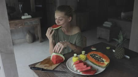 papája : young happy woman or girl (vegetarian) prepared fruit plate and enjoying watermelon, papaya, pineapple., sitting on terrace or veranda on nature in the yard with swimming pool