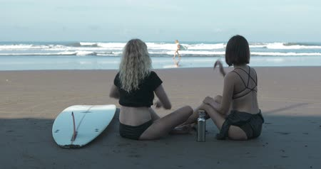 roupa de banho : two Surfer Girls Sitting On Sand, Friend Arriving With Surfboard