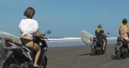 robogó : Young sexy women driving motorbikes with surfboards on the beach near the water. Shooting in motion from behind