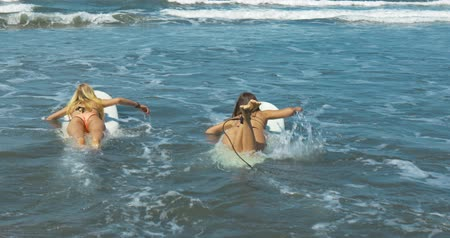 доска для серфинга : Two girls going into the ocean on their surfboards. Shot taken by a handheld gimbal
