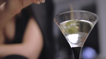 vermouth : girl throwing stick with an olive in the martini glass , cold beverage is inside, side view