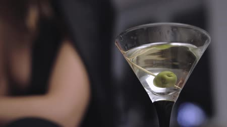 vermouth : girls or womans hand slowly dropping stick with an olive into the glass in the club, bar, restaurant. closeup Stock Footage
