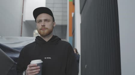 caráter : Young man walks. Handsome guy takes a paper cup of coffee from an attractive girl. City urban style. Slow motion video shooting by handheld gimbal