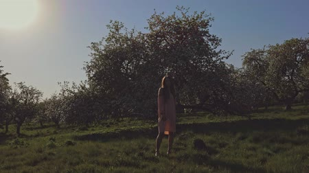 apple park : Beauty young woman enjoying nature in spring apple orchard, Happy Beautiful girl in Garden with blooming trees. Slow motion video shooting by handheld gimbal