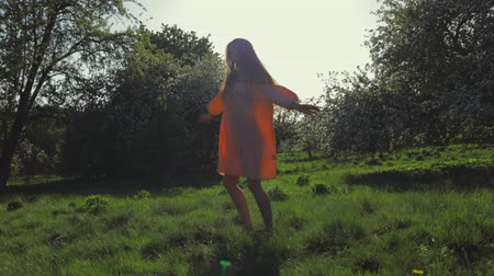 szag : Beauty young woman enjoying nature in spring apple orchard, Happy Beautiful girl in Garden with blooming trees. Slow motion video shooting by handheld gimbal