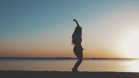 вокруг : Happy young woman dance against bright sun, turn around to express positive emotions. Elegant girl have good moments in sunny summer day. Slow motion