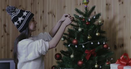 pulóver : cute nice girl wearing cap, white sweater, decorating christmas tree, red ball Stock mozgókép