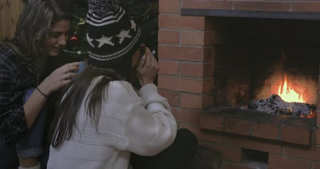 cacao : Two funny friends sitting near a Christmas tree and brick fireplace, drinking coffee, tea or cacao, laughing and smiling. Winter holidays Christmas and New Year. Stock Footage