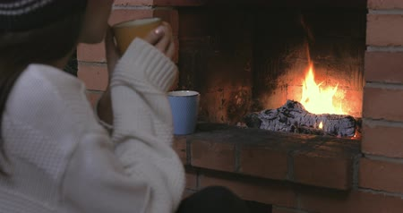 desfocado : Young girl is sitting with cup of hot drink near the fireplace, wearing sweater and cap, dreaming. Christmas mood. Unfocused