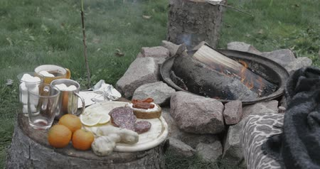 koçan : small snack and coffee break on nature, chilling and having fun outdoors near stone bonfire or campfire. little table with snacks: oranges, coffee, marshmallow, chocolate, sandwiches etc. Stok Video