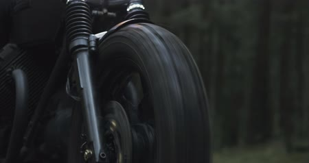 motocykl : A guy in a black leather jacket and helmet riding a classic motorcycle on a forest road. Close-up from the wheels