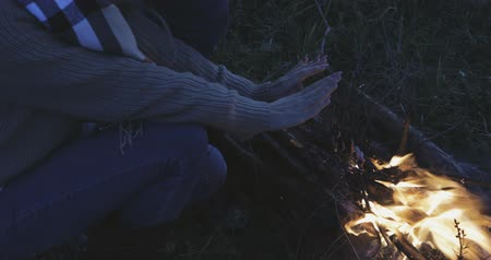 костра : young woman holding both hands above flame, thermos is lying nearby Стоковые видеозаписи