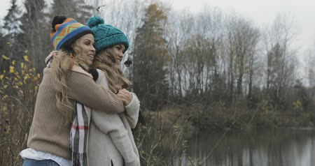 sourozenci : young pretty women standing on the lawn, cuddling, laughing, warm atmosphere, cold weather