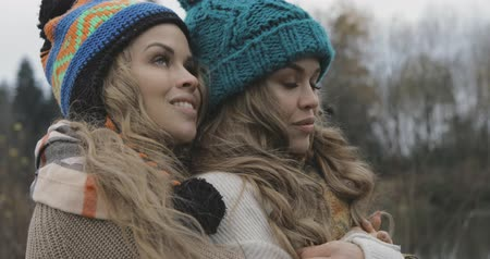 подростковый возраст : close up, beautiful sisters warming up and enjoying the view on nature, wearing sweater, hat or beanie, smiling Стоковые видеозаписи