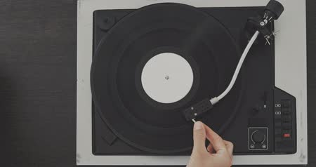 gramophone : The mans hand drops the needle on the vinyl record Stock Footage