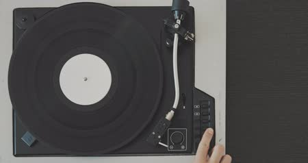 gramophone : The male hand removes the needle from the vinyl record and stops the player.
