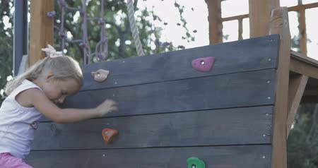 alpinism : Cute little girl child climbing up wall outside. 4k video shooting by handheld gimbal Stock Footage