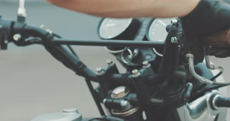 kavramak : Motorbike handle grips. Close up the hand of the motorcyclist holds the trottle and pushes the brake lever. The biker inserts the key into the ignition lock and turns the bike.