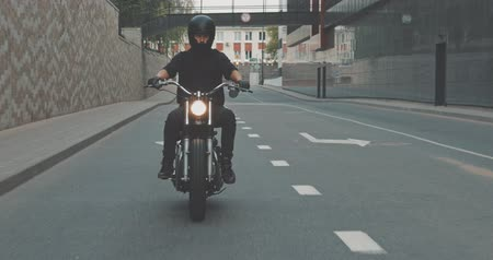 racers : Motorcyclist drives on a motorcycle on the road in the city. Biker rides a vintage custom motorbike from 1970s . Urban lifestyle scene. Front view 4K video shooting by handheld gimbal Stock Footage