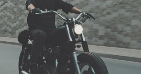 personalizado : Motorcyclist drives on a motorcycle on the road in the city. Biker rides a vintage custom motorbike from 1970s . Urban lifestyle scene. Front view 4K video shooting by handheld gimbal Vídeos