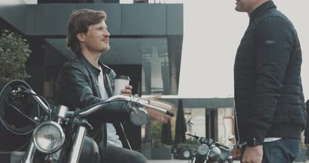 motocyklista : Two friends motorcyclists men meet on the street and shake hands with each other. Guys bikers in the leather jackets talking. Urban lifestyle scene. 4K video shooting by handheld gimbal