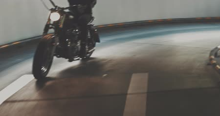 racers : Motorbiker riding on a motorcycle in the parking lot in the city. Biker rides a vintage custom motorbike from 1970s in the garage. 4K video shooting by handheld gimbal