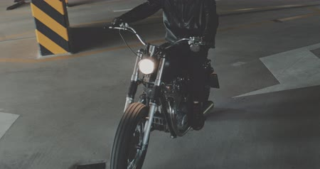 personalizado : Motorbiker riding on a motorcycle in the parking lot in the city. Biker rides a vintage custom motorbike from 1970s in the garage. 4K video shooting by handheld gimbal