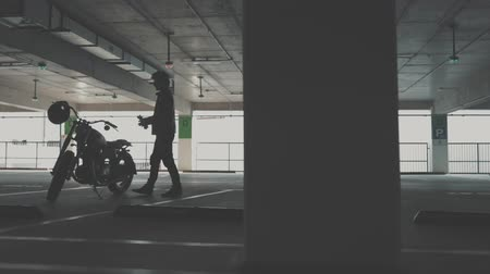 motorcycles : Biker guy walking through the parking to his motorcycle. Motorcyclist and vintage motorbike from 1970s in the garage. Side view urban lifestyle scene. Slow motion video shooting by handheld gimbal