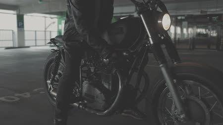 garagem : Close up of hand of the motorcyclist inserting the key into the ignition lock and turn off the engine of the bike. Urban lifestyle scene. Slow motion video shooting by handheld gimbal
