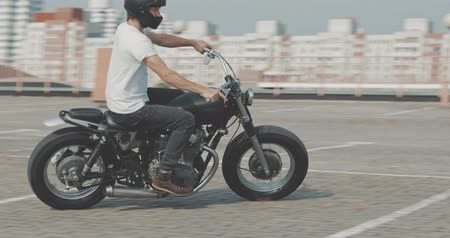 garagem : Motorcyclist drives on a motorcycle on the road in the city. Biker rides a vintage custom motorbike from 1970s . Urban lifestyle scene. 4K video shooting by handheld gimbal