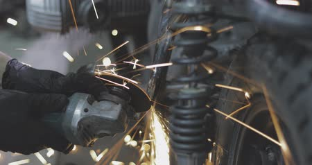 piŁa : Man works circular saw. Flies of spark from hot metal. Handsome guy working with custom motorcycle in the garage. Close-up of hand and electric saws metal hand tool