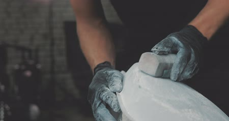 personalizado : Guy polishing metal gas tank with sandpaper. Auto mechanic assembles custom motorcycle in his workshop. Guy create an exclusive motobike cafe racer in the garage.
