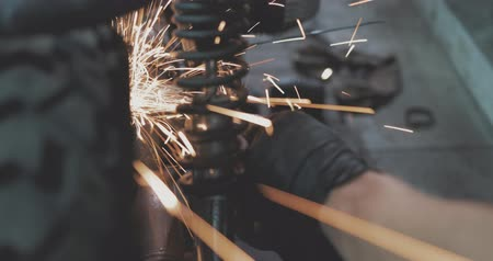 personalizado : Man works circular saw. Flies of spark from hot metal. Handsome guy working with custom motorcycle in the garage. Close-up of hand and electric saws metal hand tool