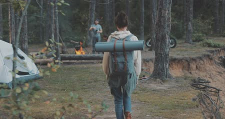 pozdravit : Young woman hiking in forest. Hiker camping in woods. Tourist walking along the river. Girl greeting friends sitting by campfire in camp. 4K video shooting by handheld gimbal