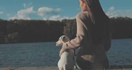 zvedák : Woman sitting by lake with dog. 4K video shooting