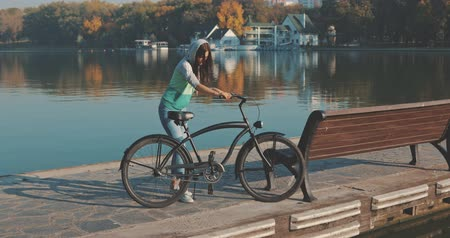 cyclette : Beautiful summertime mood shot of young woman or girl riding bicycle through promenade in sun light, 4K video shooting by handheld gimbal Filmati Stock