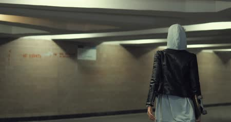 crossway : Girl teenager going at night in the underpass. Young caucasian woman with skateboard in dark underground tunnel. Urban city lifestyle. 4K video shooting by handheld gimbal