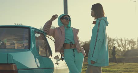 menta : Young pretty women wearing hoodie standing near mint green car at parking. Urban city lifestyle. 4K video shooting by handheld gimbal