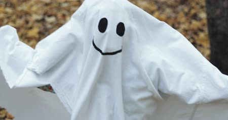 obrus : Little girl in a costume ghost with orange pumpkin. Halloween celebration holiday. Funny smiling grimace Wideo