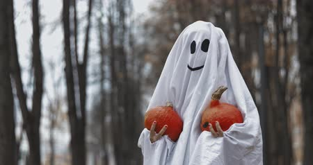 dead forest : Little girl in a costume ghost with orange pumpkin. Halloween celebration holiday. Funny smiling grimace Stock Footage