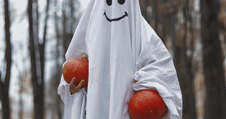 しかめっ面 : Little girl in a costume ghost with orange pumpkin. Halloween celebration holiday. Funny smiling grimace 動画素材